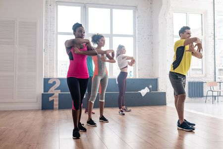 Side view of handsome trainer practicing movements with multiethnic dancers in dance studio