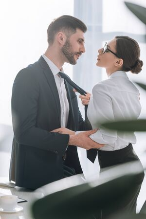 side view of businessman and secretary having love affair in office