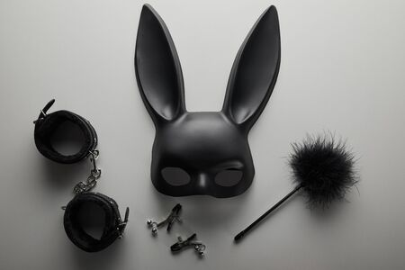top view of black rabbit mask and sex toys on white background