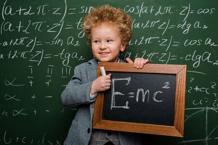 cheerful kid in suit and bow tie holding small blackboard with formula near chalkboard