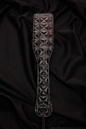 top view of leather paddle on black textile background