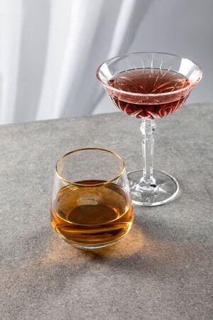 glass of cognac near red wine on white Reklamní fotografie