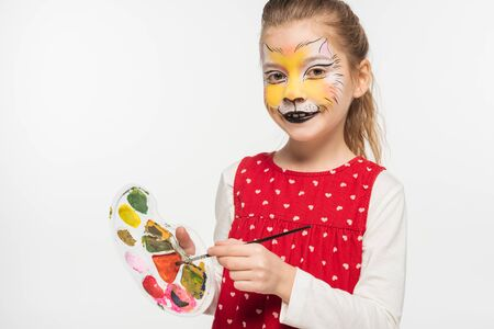 cute child with tiger muzzle painting on face holding palette and paintbrush while looking at camera isolated on white Foto de archivo