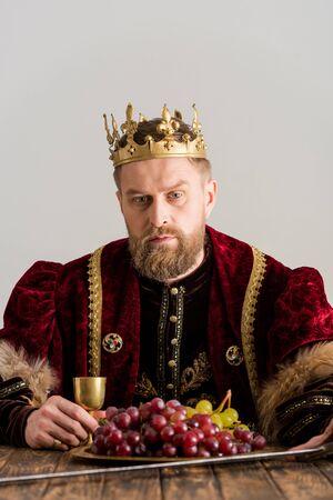 re con corona seduto a tavola isolato su gray