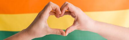 panoramic shot of woman showing heart with hands on orange, yellow and green, human rights concept