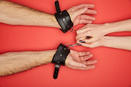 cropped view of woman holding handcuffs on man isolated on red Stock Photo