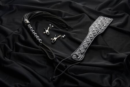 leather and metal sex toys on black textile background