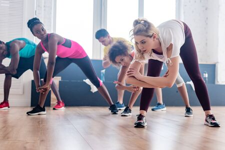 Low angle view of trainer stretching with multiethnic zumba dancers in studio