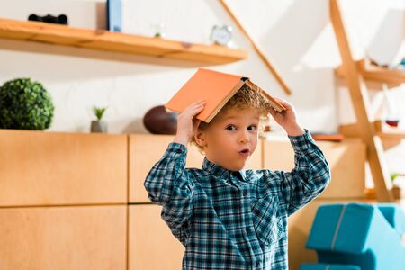 surprised and smart child holding book above head at home Standard-Bild