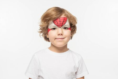 cute boy with spiderman mask painted on face smiling at camera isolated on white