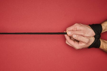 cropped view of man with rope on hands isolated on red 스톡 콘텐츠