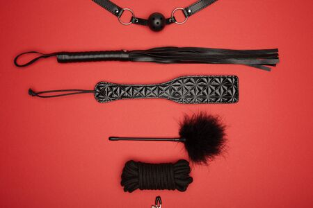 top view of black paddle, gag, rope, feather tickler and flogging whip isolated on red Archivio Fotografico