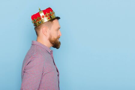 side view of handsome man with crown isolated on blue