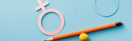 panoramic shot of scale of small ball and pencil with different genders isolated on blue, equality concept