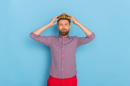 handsome man in shirt wearing crown on blue background 写真素材