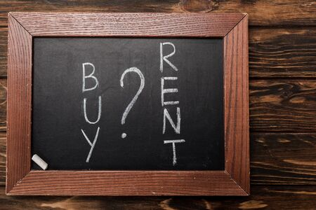 top view of chalkboard with buy and rent lettering on wooden surface Stock Photo