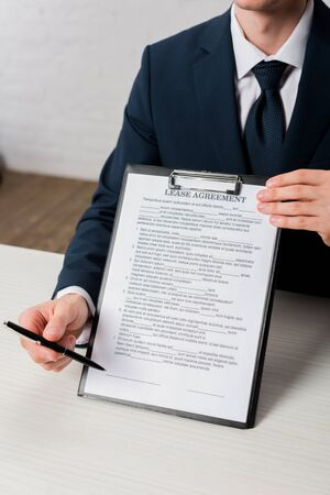 cropped view of agent holding clipboard with lease agreement lettering and pen
