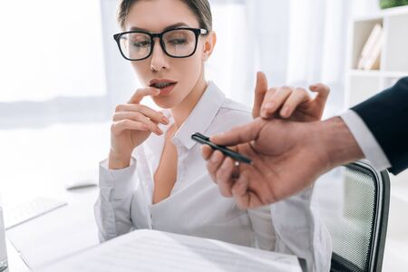 cropped view of businessman giving pen to businesswoman with big breast in office 스톡 콘텐츠