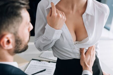 cropped view of businessman hugging sexy secretary with big breast in office