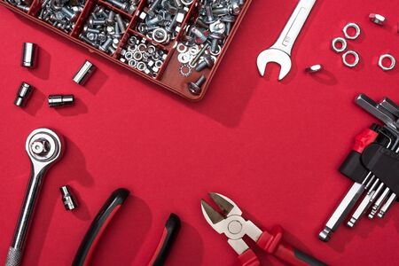 Frame of tool set with wrenches and hex keys on red background