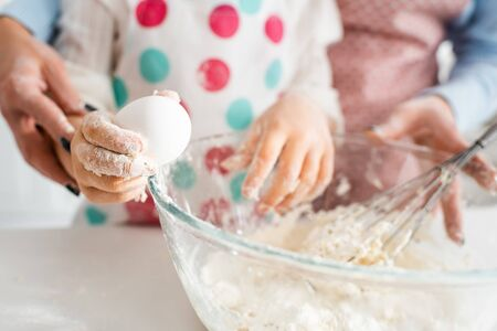 Selective focus of child holding egg near bowl and kneading dough for delicious cupcakes with mom