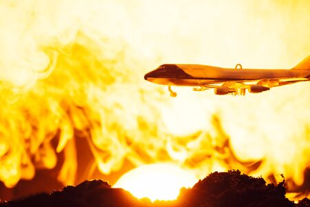 Battle scene with toy plane and fire with sunset at background Stock fotó