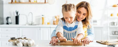 panoramic shot of smiling mother and cute daughter rolling dough on table