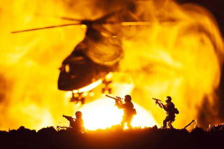 Battle scene with toy warriors and helicopter in smoke with sunset at background