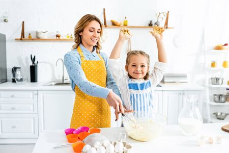 smiling mother and daughter in aprons mixing dough in kitchen Reklamní fotografie