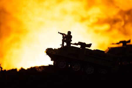 Silhouette of toy soldier on tank with fire at background, battle scene
