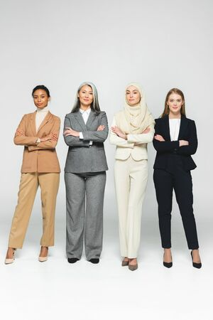 beautiful multicultural women standing with crossed arms on white