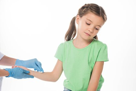 Pediatrician with cotton wool rubbing hand of kid isolated on white