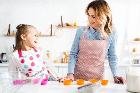 smiling mother and daughter in aprons looking at each other