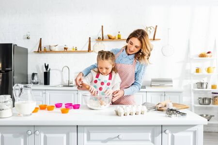 Beautiful attractive mother standing behind cute daughter while kneading dough