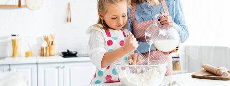 Daughter kneading dough while mother pouring milk from jug in bowl, panoramic shot