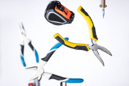 Selective focus of pliers, soldering iron and measuring tape levitating in air isolated on white 版權商用圖片