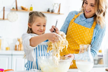 cropped view of smiling mother and daughter cooking dough