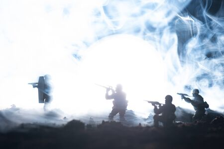 Battle scene with toy soldiers in smoke on black background Stock fotó