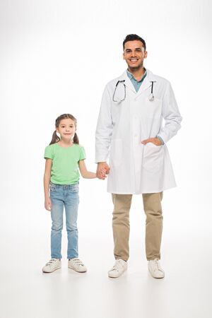Full length of smiling pediatrician and kid holding hands and smiling at camera on white background Stock fotó