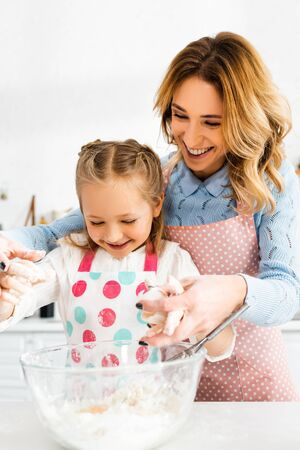Selective focus of attractive mom and cute daughter smiling and mixing ingredients for tasty cupcakes together