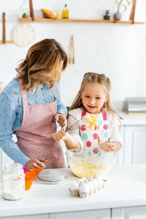 mother looking at cute and shocked daughter with balloon whisk Reklamní fotografie