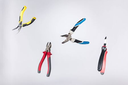 Metal pliers levitating in air isolated on grey