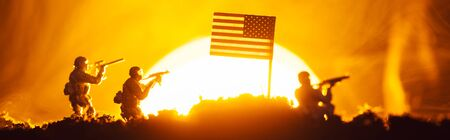 Battle scene with toy warriors near american flag in smoke with sunset at background, panoramic shot Stock fotó