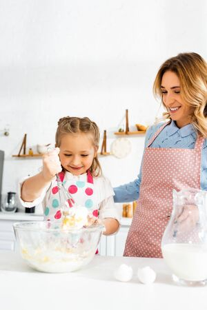 Selective focus of mother and daughter smiling and making dough for delicious cupcakes together