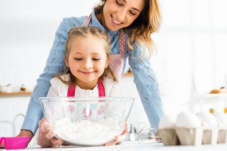 Selective focus of smiling mother and daughter near bowl with flour at kitchen table Reklamní fotografie
