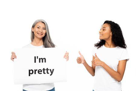 Feliz mujer afroamericana mostrando el pulgar hacia arriba cerca de soy bastante cartel aislado en blanco