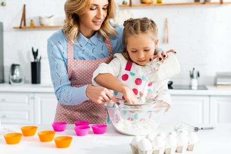 Beautiful mother and cute daughter sifting flour through sieve into bowl