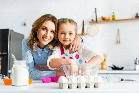 Selective focus of mother and daughter preparing dough for cupcakes in kitchen Reklamní fotografie