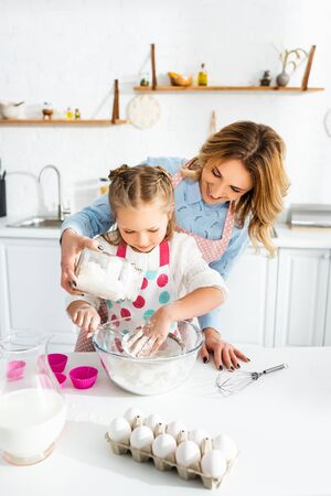 Beautiful mother and cute daughter sifting flour into bowl on table near dough molds, eggs, jug of milk and balloon whisk Reklamní fotografie