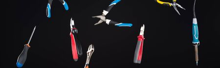 Wrenches, screwdriver and pliers levitating in air isolated on black, panoramic shot